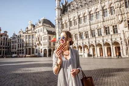A woman eating a Belgian waffle in Brussles